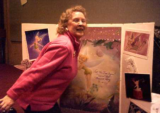 Hostess Margaret Kerry poses in front of a Tinkerbell board.