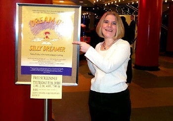 Animated News & Views' Lindsay Mayer stands next to a poster for DREAM ON, SILLY DREAMER.
